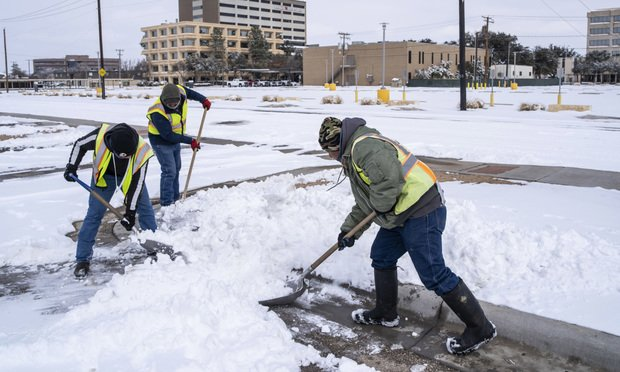 Workers clear snow from a parking lot in Midland, Texas, U.S, on Monday, Feb. 15, 2021. Blackouts triggered by frigid weather have spread to more than four million homes and businesses across the central U.S. and extended into Mexico in a deepening energy crisis that's already crippled the Texas power grid. Photo: Matthew Busch/Bloomberg