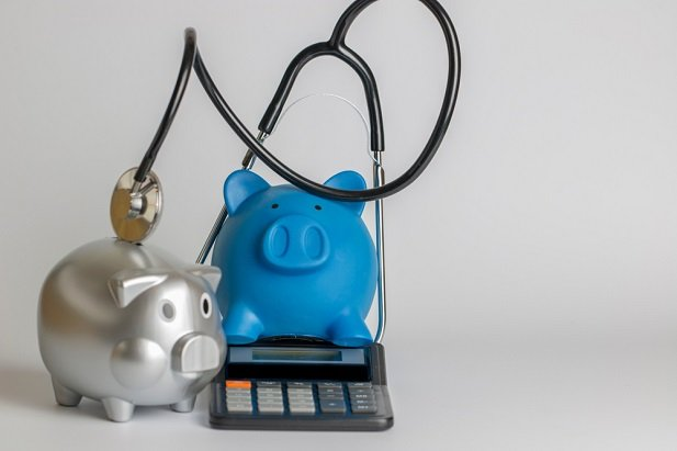 Piggy banks with calculator and stethoscope