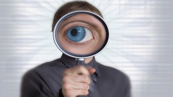Businessman with magnifying glass in front of face