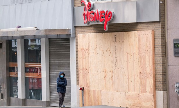 Person wearing mask in front of boarded-up Disney store.